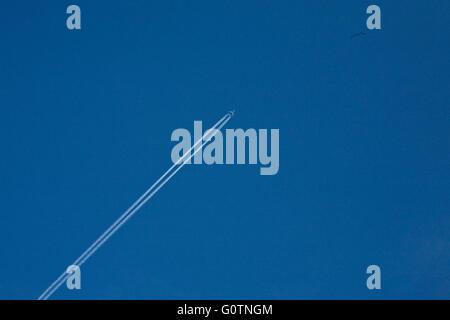 Aeroplano vola alto oltre i cieli a Henley con getto contro un cielo blu Foto Stock