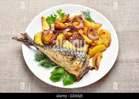 Frittura di pesce sgombro e Spicchi di patate su piastra Foto Stock