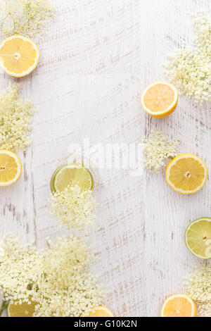 Lâ Elderflower cordiale e gli ingredienti. In casa sambuco cordiale con i limoni e elderflowers su un tavolo rustico. Foto Stock