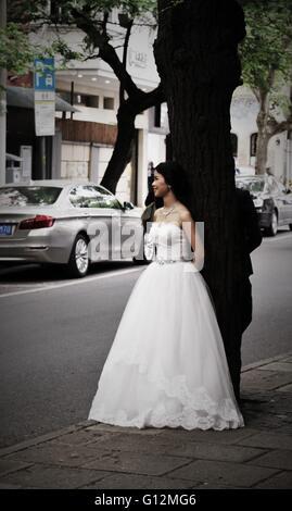 Bella sposa cinesi in un abito bianco appoggiato su di un albero in Cina a Shanghai. Foto Stock