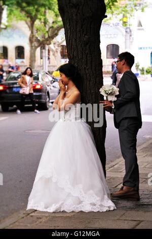 Carino sposa appoggiata sul tronco di albero e lo sposo di nascondersi dietro la struttura ad albero nella concessione Foto Stock