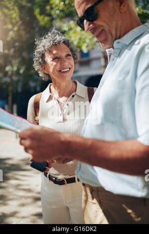 Coppia matura usando la mappa mentre si cammina intorno ad una città. Uomo mappa di lettura e donna sorridente. Foto Stock