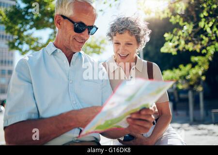 Coppia di anziani seduti all'aperto e utilizzando una mappa della citta'. Felice coppia in pensione alla ricerca Foto Stock