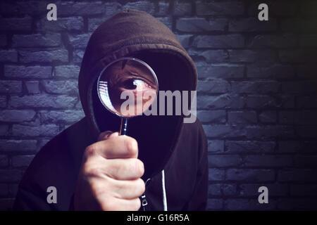 Incappucciati hacker con lente di ingrandimento, hacker di internet e la sicurezza online concetto. Foto Stock