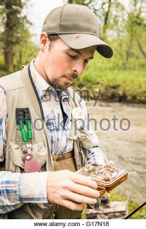 L uomo dal fiume di selezione di pesca dal fly box Foto Stock