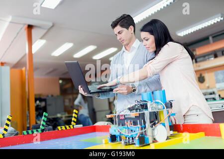 Due studenti smart di programmazione di un robot su un computer portatile Foto Stock