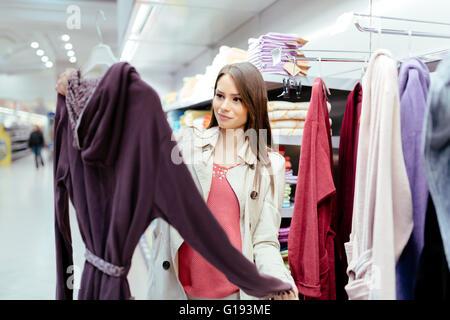Bella donna percorrendo i vestiti Foto Stock