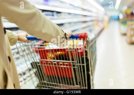 Donna spingendo carrello della spesa in un supermercato Foto Stock