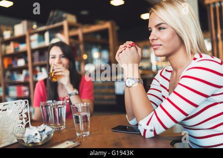 Bella donna di riposo in cafe spettegolare e parlare con gli amici Foto Stock