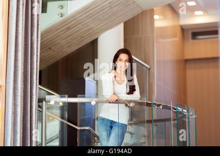Bella donna fiducioso in posa sulle scale Foto Stock