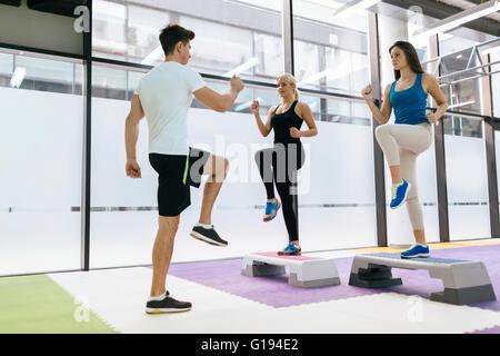 Personal trainer esercitando con aerobica tirocinanti nel fitness club Foto Stock