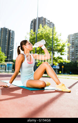 Giovane donna bella acqua potabile dopo esercizio in una città corte di formazione in una giornata di sole Foto Stock