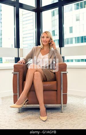 Allegro business donna seduta su una sedia. sul telefono cellulare in un ufficio moderno