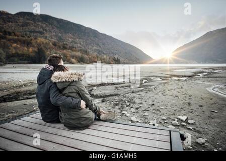 Amare giovane seduto su di un molo, abbracciando e guardando lontano, di amore e di sentimenti concept Foto Stock