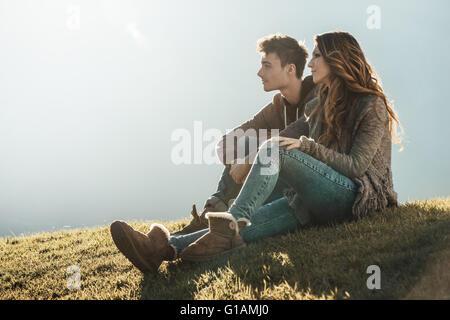 Sorridente coppia giovane seduto sull'erba durante una giornata di sole, guardando lontano e sognare il loro futuro Foto Stock