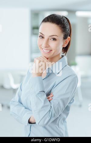 Fiducioso donna in posa con la mano sul mento e sorridente in telecamera Foto Stock