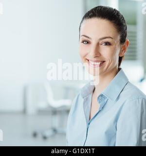 Giovane e bella sorridente business donna sorridente e guardando la telecamera, ufficio interno sullo sfondo Foto Stock