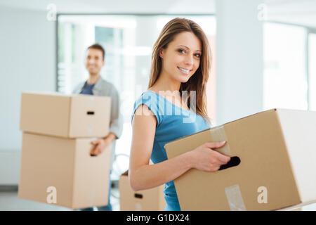 Sorridenti giovane che si muove in una nuova casa e il trasporto di scatole di cartone, delocalizzazioni e concetto di rinnovamento Foto Stock