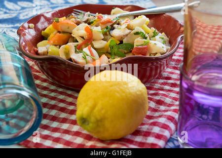 Insalata di mare con verdure e patate in una zuppiera rosso Foto Stock