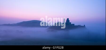 Una nebbiosa mattina a Corfe Castle nel Dorset. Foto Stock