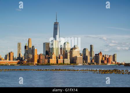 New York City Manhattan Financial District grattacieli e sul fiume Hudson con palificazioni di legno al tramonto Foto Stock