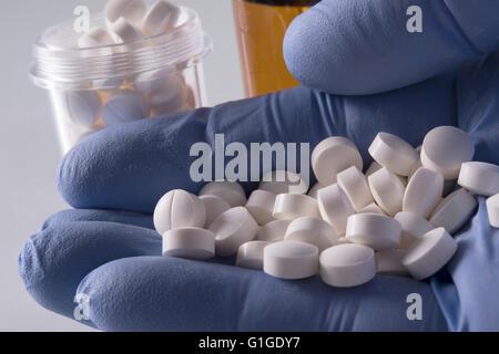 Blue mano guantata azienda pillole di bianco con i farmaci di bottiglie in background Foto Stock