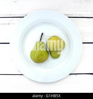 Due metà di pera su una piastra bianca su un retro bianco sullo sfondo di legno Foto Stock