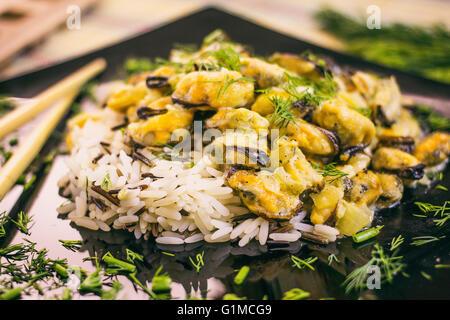 Cozze con riso in salsa cremosa di colore nero piastra di vetro Foto Stock