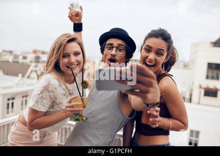 Emozionato i giovani prendendo autoritratto con telefono cellulare durante una festa. Felice giovane uomo e donna Foto Stock