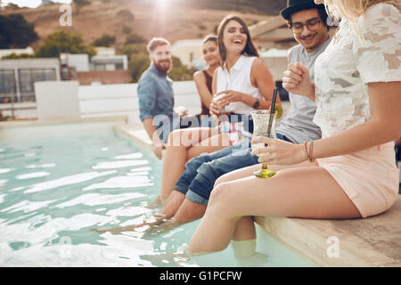 Colpo di giovani bere cocktail la piscina. Gli amici di seduta sul bordo della piscina con i piedi nell'acqua. Rilassante Foto Stock
