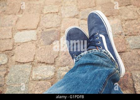 Rilassante piedi maschili in tela blu scarpe sportive su vecchi ruvida pavimentazione in pietra Foto Stock