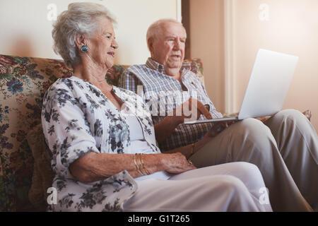 Piscina colpo di coppia senior seduta su un divano con un computer portatile. Il vecchio uomo e donna relax su un Foto Stock
