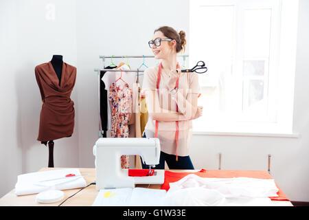 Allegro attraente giovane donna sarta con forbici e permanente smilig in design studio