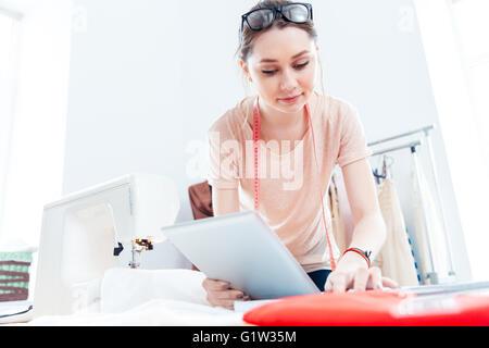 Grave giovane e bella donna sarta con la compressa a lavorare e pensare in officina Foto Stock