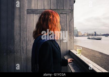 Una giovane donna è in piedi su una terrazza in legno dal fiume con un bicchiere di birra Foto Stock