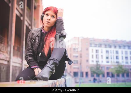 Giovane bella capelli rossi donna venezuelana ascolto di musica con cuffie, affacciato sul serio - musica, pensieroso, Foto Stock