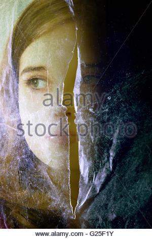 Ragazza faccia dietro un foglio di plastica con un taglio nel mezzo Foto Stock