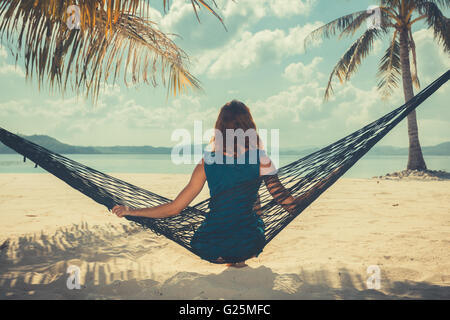 Vintage filtrata colpo di una giovane donna seduta in un'amaca su una spiaggia tropicale Foto Stock
