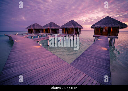 Over water bungalows con passi nel magnifico verde laguna con corallo, Maldive Sunset beach Foto Stock