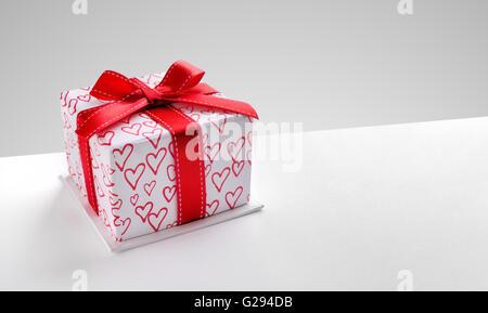 Decorativi scatola regalo con un nastro rosso e il cuore stampato sul tavolo bianco. Vista superiore sinistra. Sfondo grigio. Composizione orizzontale. Foto Stock