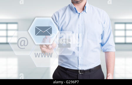 Contattaci tramite posta elettronica concetto con uomo premendo il pulsante sul futuristico trasparente dello schermo Foto Stock