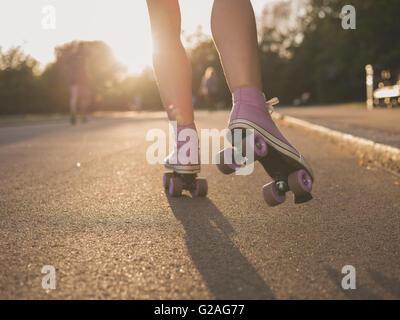 Le gambe di una giovane donna come lei è il pattinaggio a rotelle in un parco al tramonto