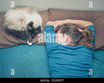 Una giovane donna è dormire in un letto con un gatto accanto a lei Foto Stock