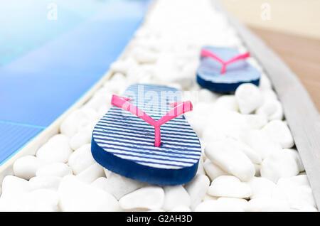 Il flip flop presso la piscina sulla ghiaia bianca. Close-up. Foto Stock