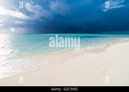 Bianca spiaggia tropicale delle Maldive con laguna blu e una tempesta tropicale Foto Stock