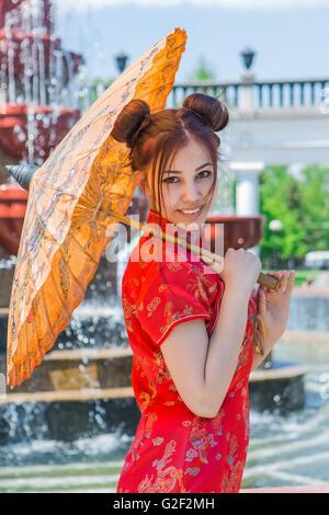 Bella ragazza asiatica in cinese tradizionale abito rosso con ombrello di bambù vicino alla fontana Foto Stock