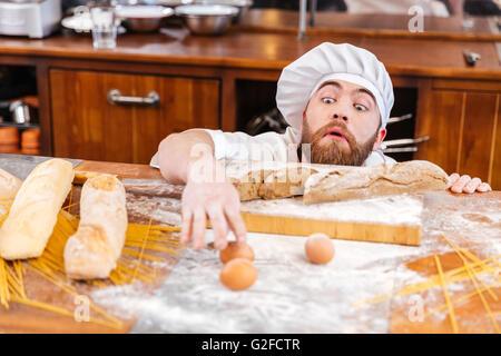 Carino divertente baker con la barba scherzando e divertendosi in cucina Foto Stock