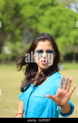 Una giovane bella ragazza ritratto con fermata a mano segno di espressione Foto Stock