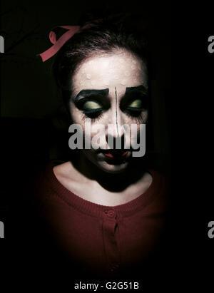 Donna con dipinto Clown-Like faccia rivolta verso il basso Foto Stock