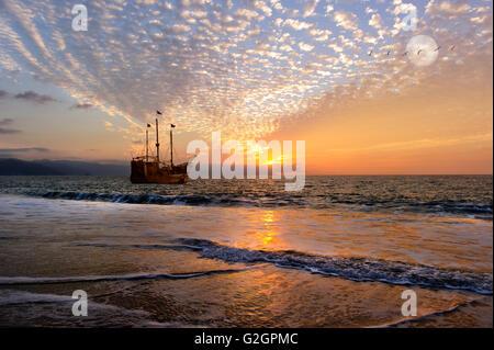 La nave dei pirati fantasy è un vecchio di legno la nave dei pirati con bandiere completo come il sole tramonta Foto Stock